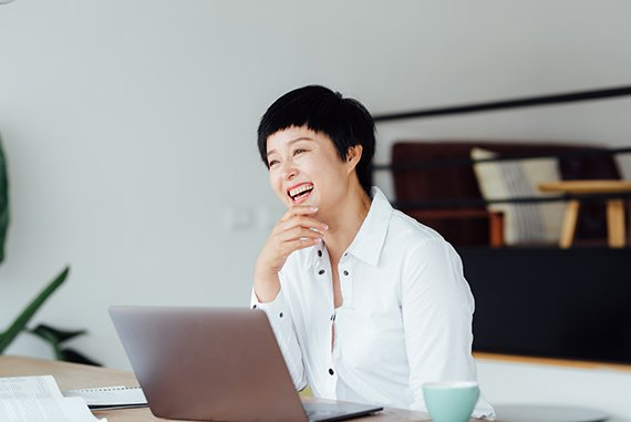 Asian woman smiling and using laptop as a image of Scilife's customers.