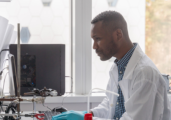 Male Scientist working on his computer at a lab.